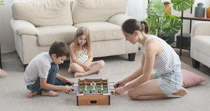 Family playing foosball at home. Mother with her children having fun playing foosball at home stock footage