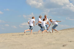 Family playing football on a beach. Big Family playing football on a beach in summer day Stock Photo