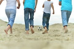 Family playing football on a beach. Big Family playing football on a beach in summer day Royalty Free Stock Images