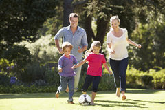 Family Playing Football In Garden Together Stock Photo