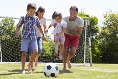 Family Playing Football In Garden Together Stock Photography