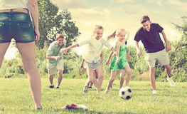 Family playing in football outdoors on summer sunny day Royalty Free Stock Image