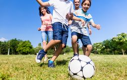 Family playing football or soccer in park stock photos
