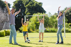 Family playing football together at the park Stock Photography