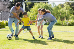 Family playing football together at the park Stock Images