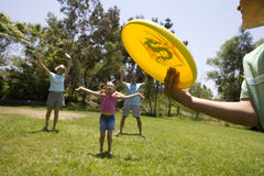 Family playing frisbee in park, boy (9-11) throwing disc to parents, girl (7-9) in middle Stock Image