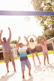 Family Playing Game Of Volleyball In Garden Stock Image