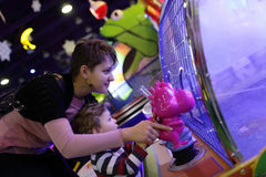 Family playing with gaming machine. At an amusement park Royalty Free Stock Photos