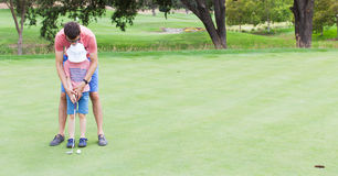 Family playing golf. Panorama of family at golf field, father teaching his son to play golf Stock Photo