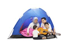 Family playing a guitar in a camping tent. Happy family with two children playing a guitar in a camping tent, isolated on white background stock photos