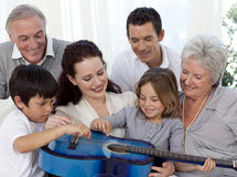 Family playing a guitar in living-room. Smiling family playing a guitar in living-room royalty free stock photo