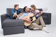 Family playing on guitar and singing, spending time together while sitting on sofa. Happy family playing on guitar and singing, spending time together while stock image