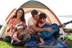Family playing a guitar in a tent Stock Image