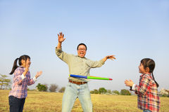 Family playing with hula hoops outdoors Stock Images