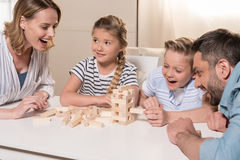 Family playing Jenga game at home together. Smiling family playing Jenga game at home together Stock Images