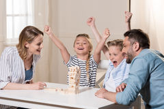 Family playing Jenga game at home together. Smiling family playing Jenga game at home together Stock Image