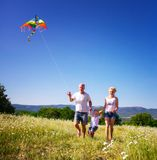 Family playing with kite. On the flower meadow Stock Photo