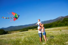 Family playing with kite Stock Photos