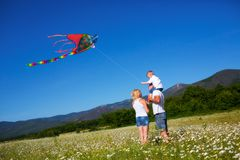 Family playing with kite. On the flower meadow Royalty Free Stock Photos