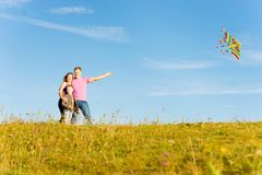 Family playing with a kite. Happy family playing with kite in a park Stock Images