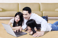 Family playing laptop on the floor at home Stock Image