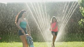 Family Playing on the Lawn Water Sprinkling on Mother with Children stock video footage