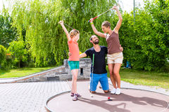 Family playing miniature golf. Outdoors Royalty Free Stock Photo
