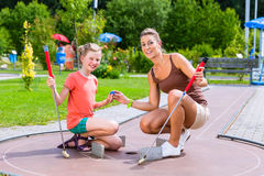 Family playing miniature golf. In summer Royalty Free Stock Photos