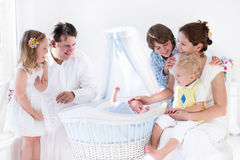 Family playing with newborn child in white bassinet royalty free stock photography