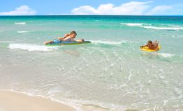Family Playing in Ocean Surf. Dad and kids playing in beach surf on boards royalty free stock images