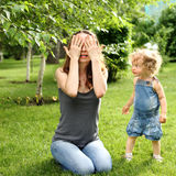 Family playing in park. Woman and child playing hide-and-seek in summer park royalty free stock photo