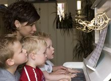 Family playing piano. A cute family picture were four people are playing the piano stock photos