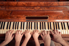 Family is playing the piano. Family of three people is playing the piano, front view Royalty Free Stock Photo