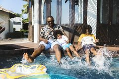 Family playing by a pool stock image