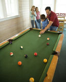 Family Playing Pool. Man and boy shooting pool with woman and girl in background. Vertically framed shot Royalty Free Stock Photography