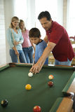 Family Playing Pool. Man and boy playing pool with woman and girl in background. Vertically framed shot Stock Images