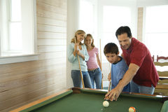 Family Playing Pool. Man and boy shooting pool with woman and girl in background. Horizontally framed shot Royalty Free Stock Photography