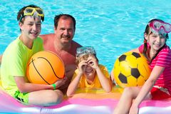Family playing in pool. Three happy children playing with father in swimming pool Royalty Free Stock Photos
