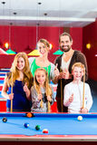 Family playing pool billiard game. Family playing together billiard with queue and balls on pool table Royalty Free Stock Photography