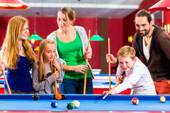 Family playing pool billiard game. Family playing together billiard with queue and balls on pool table Stock Image