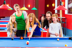 Family playing pool billiard game. Family playing together billiard with queue and balls on pool table stock photo