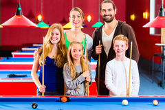 Family playing pool billiard game. Family playing together billiard with queue and balls on pool table Stock Images