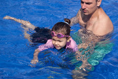Family playing in the pool. Father and daughter playing in the pool Royalty Free Stock Photo
