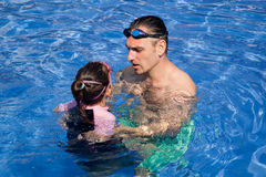 Family playing in the pool Stock Images