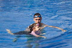 Family playing in the pool. Father and daughter playing in the pool Royalty Free Stock Images