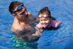 Family playing in the pool. Father and daughter playing in the pool Royalty Free Stock Photography