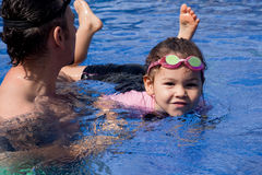 Family playing in the pool. Father and daughter playing in the pool Royalty Free Stock Photos