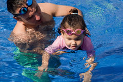 Family playing in the pool. Father and daughter playing in the pool Stock Image