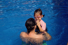 Family playing in the pool. Father and daughter playing in the pool Royalty Free Stock Image