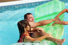 Family playing in the pool. Father and daughters playing in the pool Royalty Free Stock Image